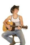 Junger Mann, der eine Gitarre mit Cowboyhutlächeln spielt Lizenzfreie Stockbilder