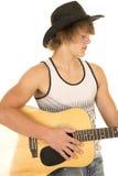 Junger Mann, der eine Gitarre mit Cowboyhutträgershirt spielt Stockfoto