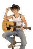 Junger Mann, der eine Gitarre mit dem Cowboyhutschauen spielt Lizenzfreie Stockfotos