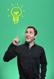 Junger Mann, der eine Idee mit Glühlampe über seinem Kopf hat Lizenzfreie Stockfotos