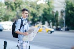 Junger Mann, der eine Karte hält Stockfotografie