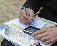 Junger Mann, der eine Karte verwenden und gps, um einen Weg zu planen Lizenzfreies Stockfoto