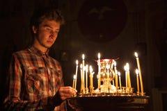 Junger Mann, der eine Kerze in der Kirche beleuchtet. Stockfotografie