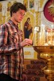 Junger Mann, der eine Kerze in der Kirche beleuchtet. Lizenzfreie Stockfotografie