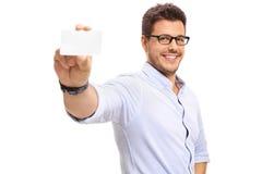 Junger Mann, der eine leere Visitenkarte zeigt Stockfoto