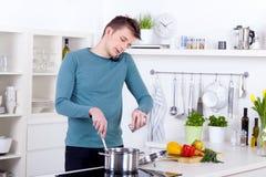 Junger Mann, der eine Mahlzeit kocht und am Telefon in der Küche spricht Lizenzfreies Stockbild