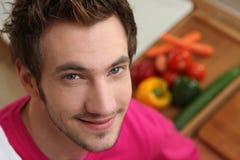 Junger Mann, der eine Mahlzeit vorbereitet stockfotografie