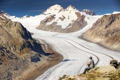 Junger Mann, der eine majestätische Ansicht zu Aletsch-glacie sitzt und genießt Lizenzfreies Stockfoto