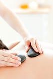 Junger Mann, der eine Massage mit heißen Steinen hat Lizenzfreies Stockfoto