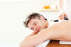 Junger Mann, der eine rückseitige Massage mit heißen Steinen genießt stockbild