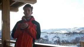 Junger Mann, der eine Schale heißen Kaffee auf einer Plattform in der Winterzeit am Berg trinkt stock footage
