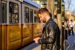 Junger Mann, der in eine Tramstation wartet Lizenzfreies Stockfoto