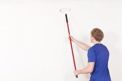 Junger Mann, der eine Wand malt Stockbild