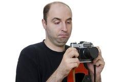 Junger Mann, der eine Weinlesekamera auf weißem Hintergrund hält Lizenzfreies Stockbild