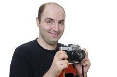 Junger Mann, der eine Weinlesekamera auf weißem Hintergrund hält Stockbild
