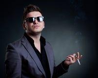 Junger Mann, der eine Zigarette raucht Lizenzfreies Stockfoto
