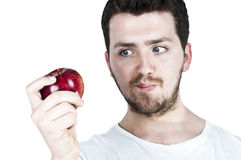 Junger Mann, der an einem Apfel straing ist Lizenzfreies Stockfoto