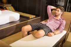 Junger Mann, der in einem Asiatisch-angeredeten Hotelzimmer sich entspannt Stockbild