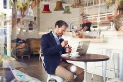 Junger Mann, der in einem Café isst einen Nachtisch sitzt lizenzfreies stockbild