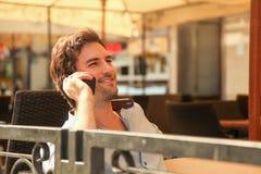 Junger Mann, der an einem Handy spricht Stockbild