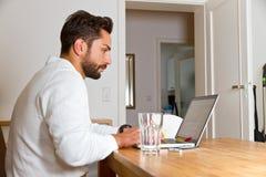 Junger Mann, der an einem Laptop arbeitet Stockfotografie