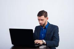 Junger Mann, der an einem Laptop arbeitet Stockfoto