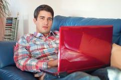 Junger Mann, der an einem Laptop im Wohnzimmer arbeitet stockfotos