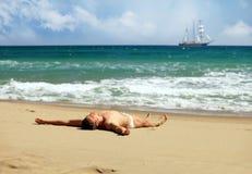 Junger Mann, der an einem Strand ein Sonnenbad nimmt Stockfotos