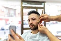 Junger Mann, der einen Bart rasiert erh?lt stockbild