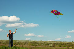 Junger Mann, der einen Drachen fliegt Lizenzfreie Stockfotos