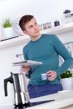 Junger Mann, der einen Espresso trinkt und die Zeitung liest stockfotografie