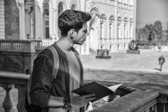 Junger Mann, der einen Führer außerhalb des historischen Gebäudes hält Stockbilder