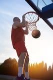 Junger Mann, der einen fantastischen Slam Dunk spielt stree springt und macht Stockfoto
