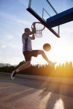 Junger Mann, der einen fantastischen Slam Dunk spielt stree springt und macht Stockbilder