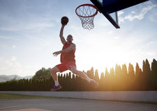 Junger Mann, der einen fantastischen Slam Dunk spielt stree springt und macht Stockfotos