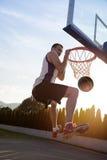 Junger Mann, der einen fantastischen Slam Dunk spielt stree springt und macht Lizenzfreie Stockfotografie