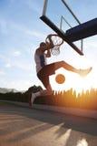 Junger Mann, der einen fantastischen Slam Dunk spielt stree springt und macht Lizenzfreies Stockbild