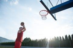 Junger Mann, der einen fantastischen Slam Dunk spielt stree springt und macht Lizenzfreie Stockbilder