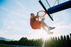 Junger Mann, der einen fantastischen Slam Dunk spielt stree springt und macht Stockbild