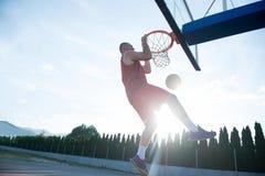 Junger Mann, der einen fantastischen Slam Dunk spielt stree springt und macht Lizenzfreies Stockfoto