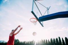 Junger Mann, der einen fantastischen Slam Dunk spielt stree springt und macht Lizenzfreie Stockfotos