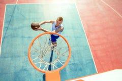 Junger Mann, der einen fantastischen Slam Dunk spielt streetball, Basketball springt und macht Städtisches authentisches Stockbilder