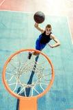 Junger Mann, der einen fantastischen Slam Dunk spielt streetball, Basketball springt und macht Städtisches authentisches Lizenzfreie Stockfotos