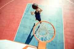 Junger Mann, der einen fantastischen Slam Dunk spielt streetball, Basketball springt und macht Städtisches authentisches Lizenzfreie Stockbilder
