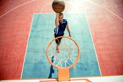 Junger Mann, der einen fantastischen Slam Dunk spielt streetball, Basketball springt und macht Städtisches authentisches Lizenzfreie Stockfotografie