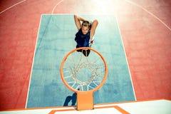 Junger Mann, der einen fantastischen Slam Dunk spielt streetball, Basketball springt und macht Städtisches authentisches Stockfoto