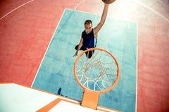 Junger Mann, der einen fantastischen Slam Dunk spielt streetball, Basketball springt und macht Städtisches authentisches Stockfotos