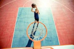 Junger Mann, der einen fantastischen Slam Dunk spielt streetball, Basketball springt und macht Städtisches authentisches Lizenzfreies Stockbild
