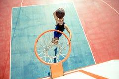 Junger Mann, der einen fantastischen Slam Dunk spielt streetball, Basketball springt und macht Städtisches authentisches Lizenzfreies Stockfoto