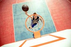 Junger Mann, der einen fantastischen Slam Dunk spielt streetball, Basketball springt und macht Städtisches authentisches Stockfotografie